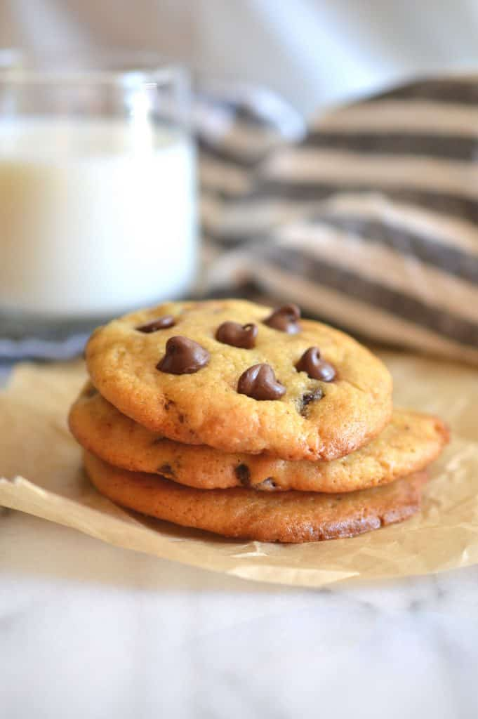 Chocolate chip cookies on parchment paper with glass of milk in the background.