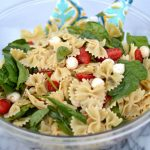 Spinach, tomato and fresh mozzarella pasta salad in a glass bowl with serving spoons.
