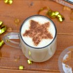 Latte with a star shaped cinnamon stenciled into the frothy milk.