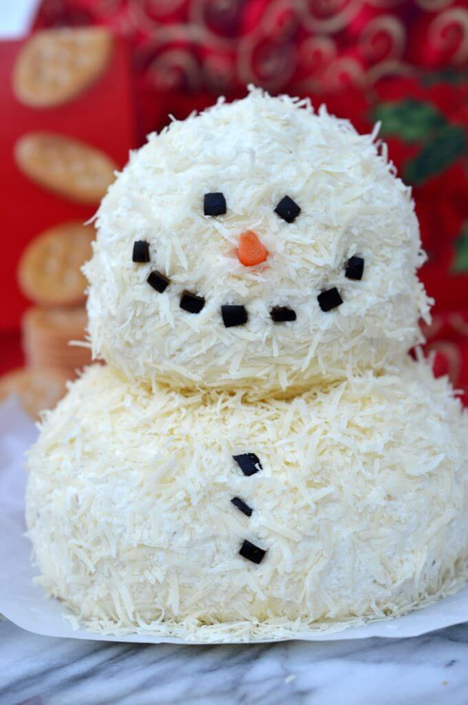 This savory Garlic Parmesan Holiday Snowman Cheeseball contains minimal ingredients and is SO impressive on a holiday platter! Dress up your appetizer spread with something new and festive this holiday season!