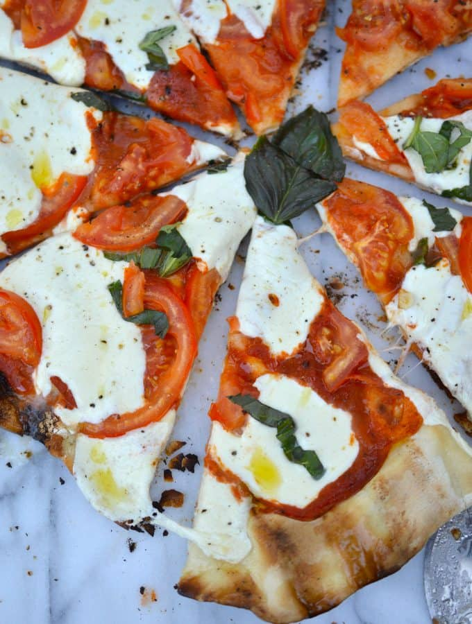 Homemade grilled pizza is perfect for when it's just too hot to turn on the oven and you don't want to order takeout! Crispy grilled crust holds your favorite toppings and deliciously melty cheese.