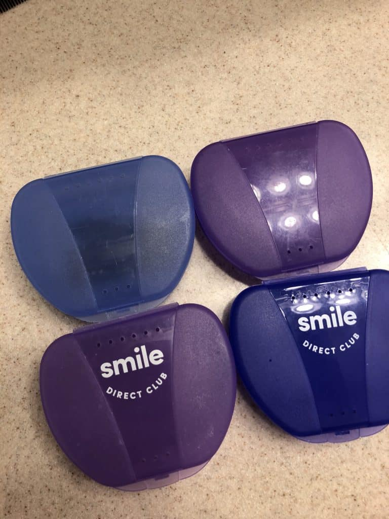 4 SmileDirectClub retainer cases on a counter.