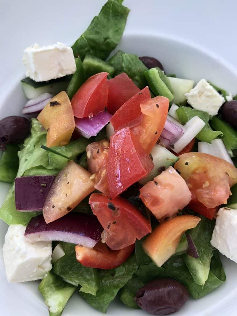 A light and refreshing Greek salad with cucumbers, lettuce, tomatoes, onions, olives and feta cheese.