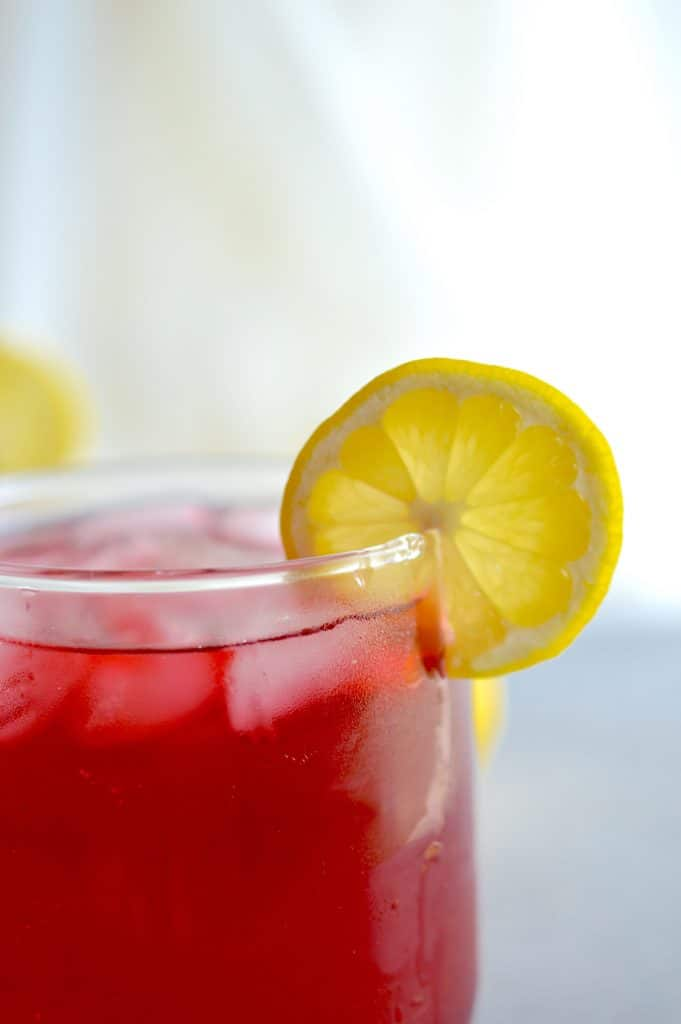 Passion Tea Lemonade in a short glass with a lemon slice on the rim.