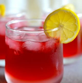 Passion Tea Lemonade in a glass with lemon slice on the rim of the glass.