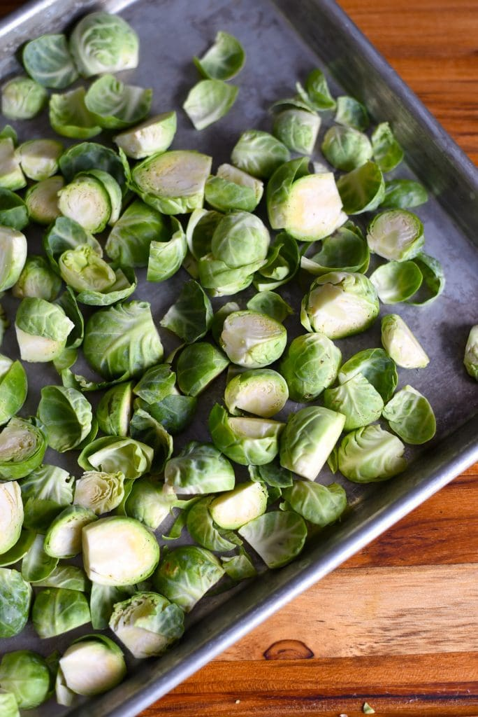Brussels sprouts cut on a baking sheet.