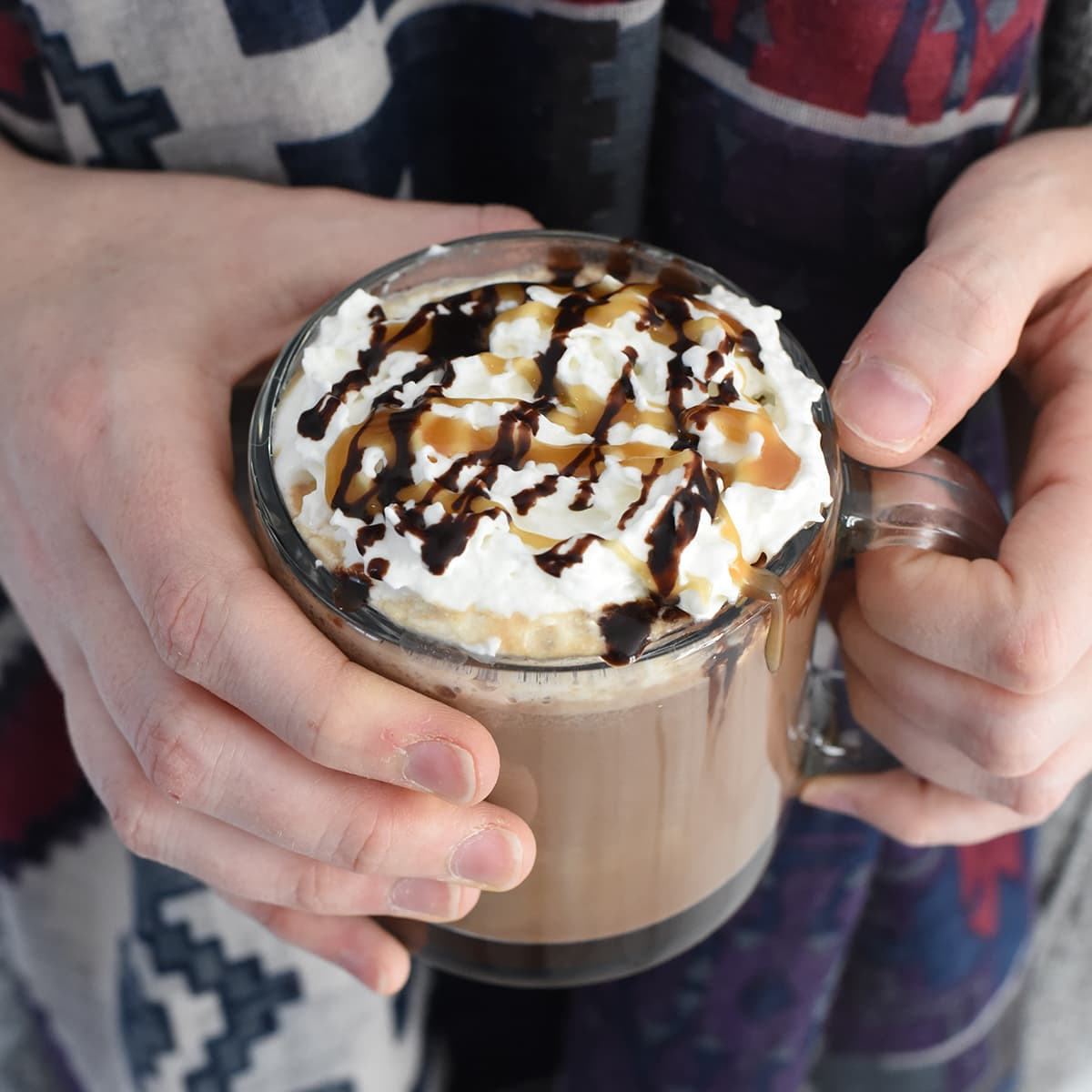 Salted caramel mocha in a glass mug being held.