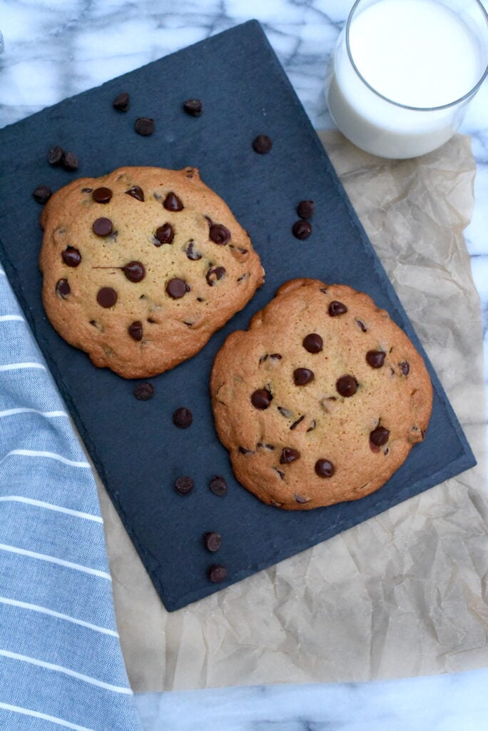Two large chocolate chip cookies on a slate surface.
