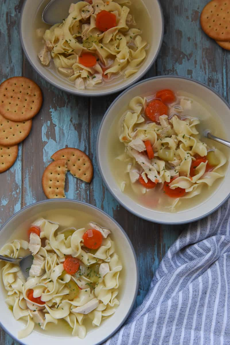 Three bowls of chicken noodle soup with egg noodles, sliced carrots, celery and onions, garnished with parsley in gray bowls.