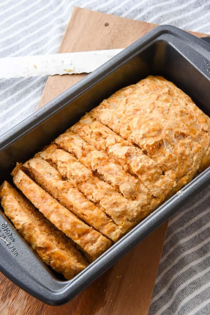 Garlic cheddar beer bread in a loaf pan, sliced.
