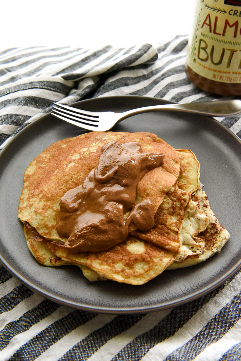 Healthy Banana Pancakes on a plate with almond butter drizzled on top.